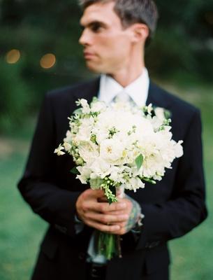 Groom in black tuxedo holds bouquet of white flowers
