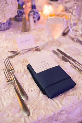 Wedding reception white menu with white rosette linen tablecloth navy blue napkin and menu nestled i