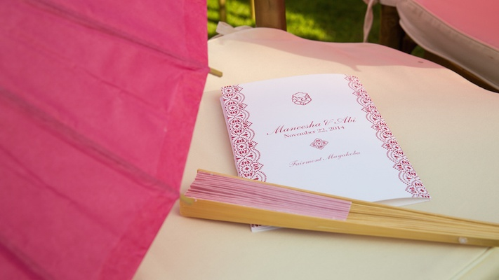 Outdoor wedding ceremony with pink parasol and fan on chair