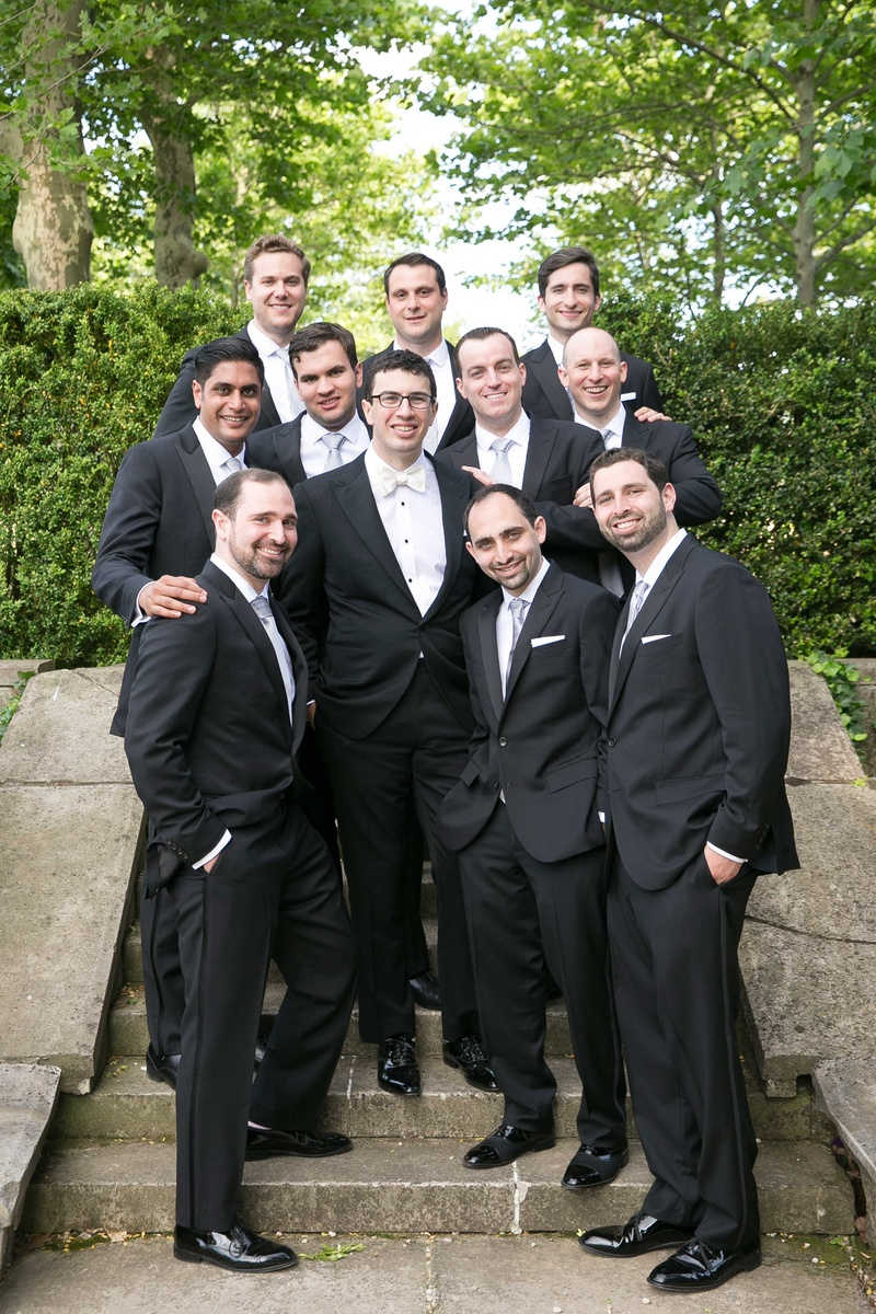Groom in tuxedo with white bow tie and groomsmen in tuxedos with silver ties