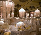 White tables and chair covers with floral centerpieces