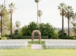 white chairs and pink floral arch on lawn surrounded by palm trees