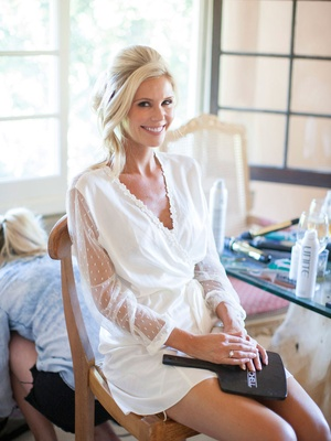 a bride in a white robe smiling in the makeup chair after getting her face done