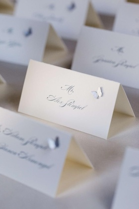 White seating card with grey lettering and applique