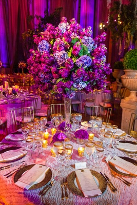 Textured linens with gilt flatware and tall floral centerpiece