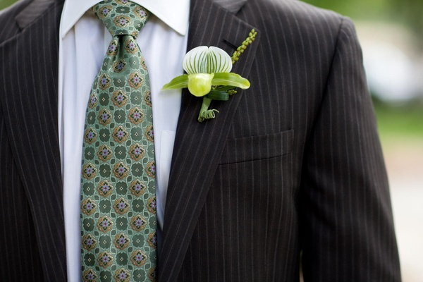 Groom in a pinstripe suit, light green tie, and lady slipper boutonniere