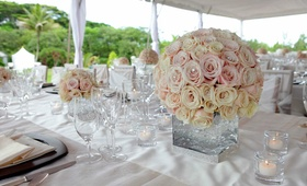 Wedding reception centerpiece of round bouquet of cream roses and light pink in a modern vase