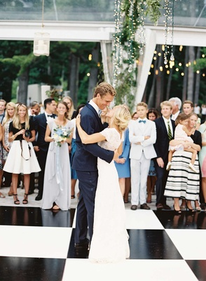 Bride in Carolina Herrera short sleeve lace wedding dress with groom in navy tuxedo on dance floor