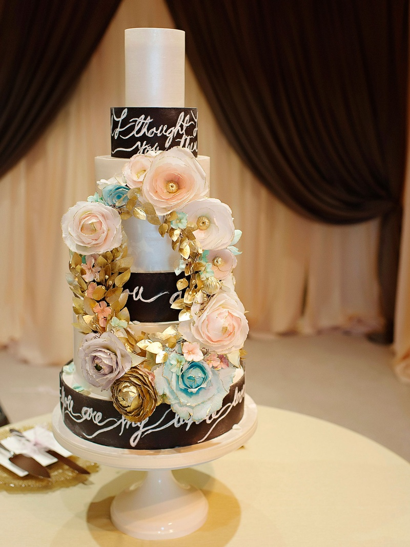 Seven layer wedding cake with song lyrics on each layer with pink blue gold sugar flower gold wreath