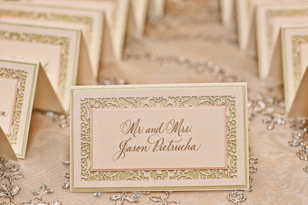 Wedding escort card in pale pink & green, gold calligraphy, laser-cut border