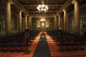 Wedding ceremony with black chairs and aisle runner at the Emerald Room of the Millennium Biltmore