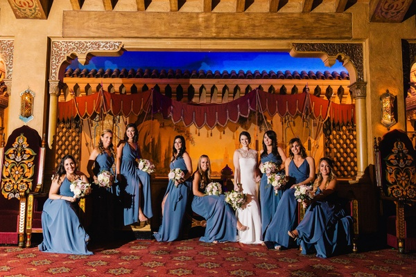 bride in lela rose, bridesmaids in joanna august floor length long blue bridesmaid dresses wrap