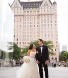 bride and groom stand looking at each other outside the plaza hotel in new york city