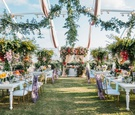 wedding reception in clear top tent greenery drapery white table gold purple chairs colorful flowers