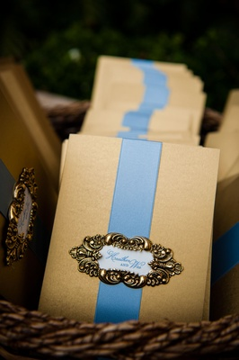 Gold ceremony program with light blue ribbon and gold filigree details