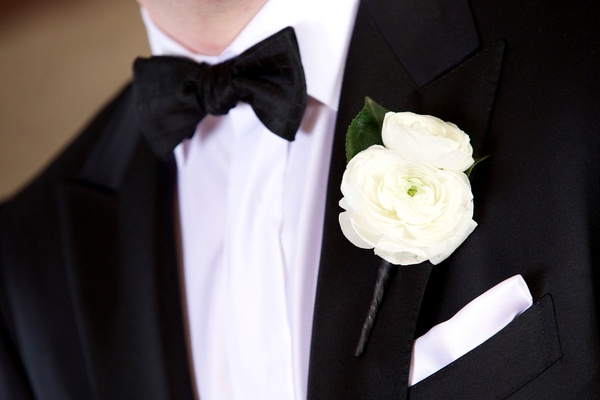 Groom's black and white tuxedo with two fresh ranunculus blooms and white pocket square