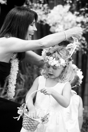 Black and white photo of woman helping flower girl with flower crown