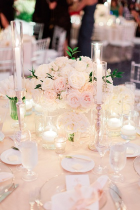 blush and ivory wedding reception with small arrangement of roses and tapered candles