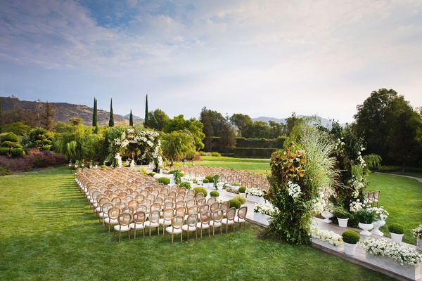 wedding ceremony westlake village green lawn wood chairs green arches white flowers