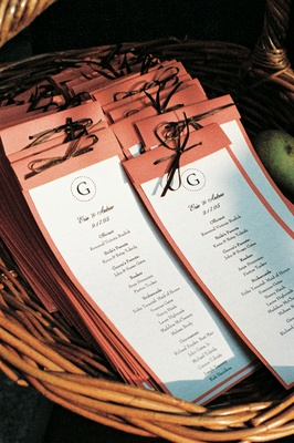Coral wedding programs tied with brown ribbon