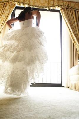 Bride walks toward bridal suite window in wedding dress