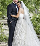 Bride in ruffle wedding dress with groom in tuxedo