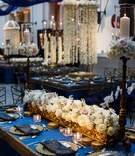 blue and gold tablescape with low white floral arrangements and high hanging centerpiece kaleera
