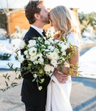 groom in brooks brothers tuxedo kisses bride on forehead, loosely structured bouquet