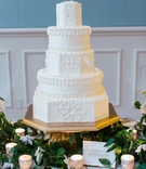 Wedding reception stand cake on gold stand white cake greenery candle votive wedding cake with dairy