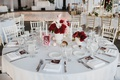 wedding reception white linens, small arrangement of white flowers and red florals, tapered candles