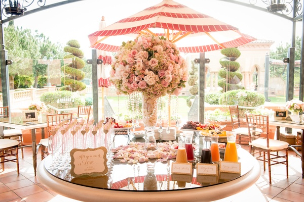 Wedding shower table with mimosa bar, fresh fruit, centerpiece of pink roses, green hydrangeas