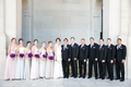 bridesmaids in muted colors and vibrant purple bouquets