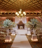 Gold wedding ballroom paneling with white delphinium flowers along aisle