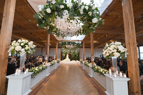 wedding ceremony wood floor aisle beams greenery wreath white flowers chandeliers candles
