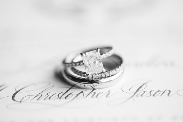 black and white photo of engagement ring with large radiant diamond and thin pavé bands