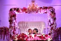 bride in glam headband with groom on throne sweetheart table arch of flowers pink fuchsia lighting
