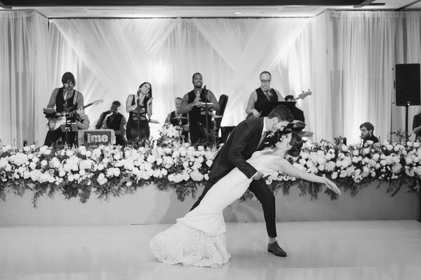 black and white photo of live band performing during first dance at wedding ballroom reception