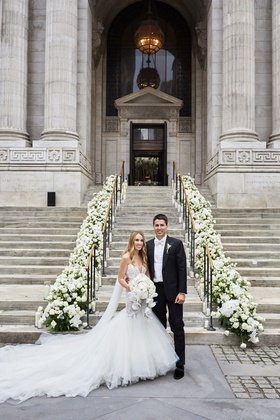 bride in galia lahav wedding dress cathedral veil groom tux white bow tie new york library steps