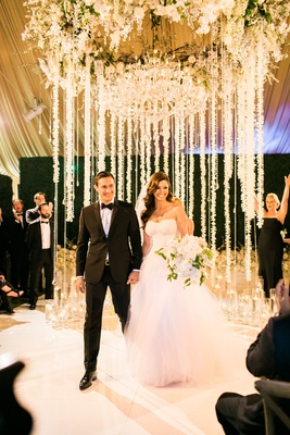 Bride in monique lhuillier wedding dress holding bouquet neutral with groom after ceremony tent