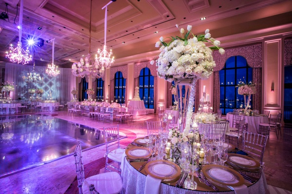 Wedding reception in ballroom pink violet lighting rose, tulip, hydrangea centerpiece in vase
