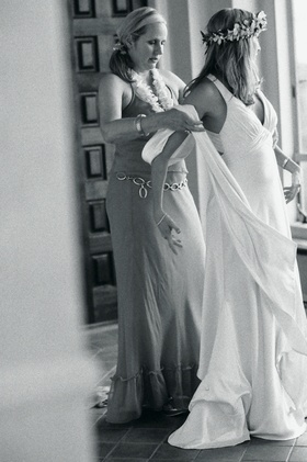 Black and white photo of woman helping bride get dressed