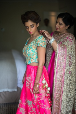 indian mother of the bride helps daughter get ready