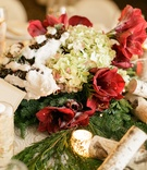 Winter wedding centerpiece of evergreen, red amaryllis, green hydrangeas, fake snow on pinecones