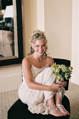 Bride wears pearl crown and necklace with shell sandals