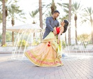 south asian wedding inspiration, bride in lehenga, groom dips bride in front of fountain