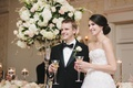 Bride and groom in formal attire smile with champagne at reception