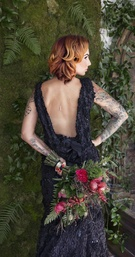 Bride in a black R-Mine Bespoke dress with appliques, cowl back, bouquet with greenery, red flowers