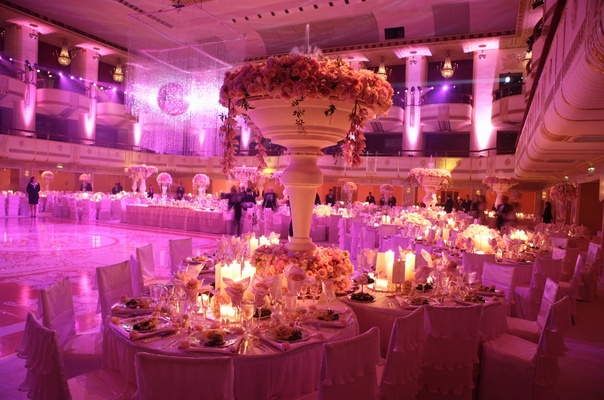 Ballroom wedding with pink lighting, crystals, and flowers