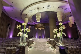 Custom lighting and illuminated floral create a wonderfully modern wedding aisle.