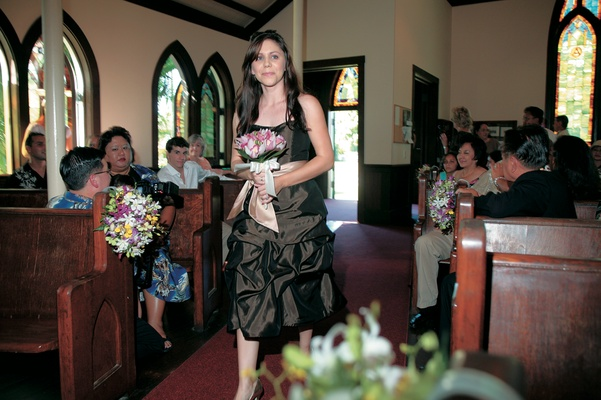 bridesmaid walks down the aisle at ceremony in hawaii